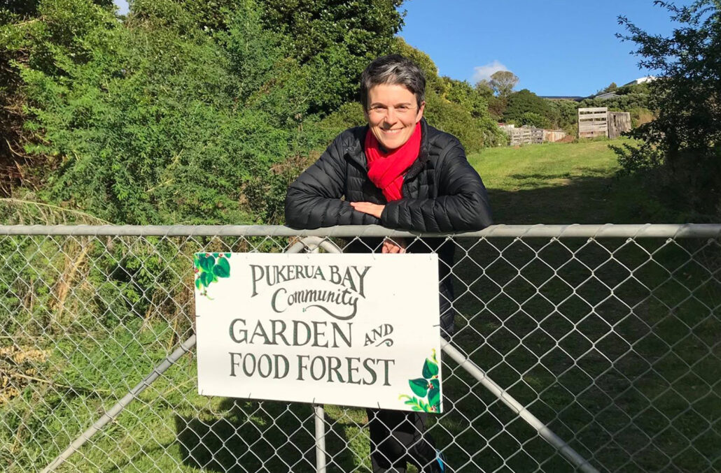 Jane smiling standing at a gate with a hand painted sign that says Pukerua Bay Community Garden and Food Forest