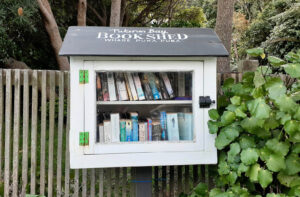 Small wooden book shed attached to a fence