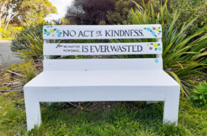 """White painted bench seat in a grassed area. The words """"No act of kindness, no matter how small, is ever wasted""""."""
