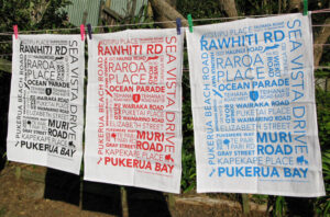 Three tea towels hanging on a clothes line. Each with a typographic design.