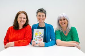 3 smiling women sat at a white table. The middle woman is holding a book.