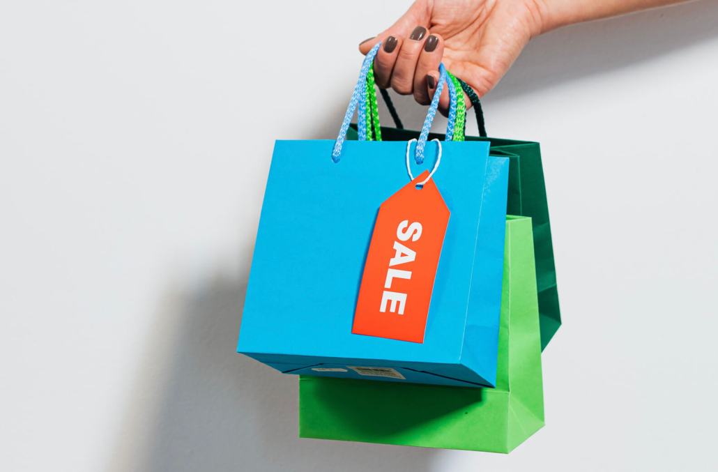 A hand holding colourful paper shopping bags on a white background