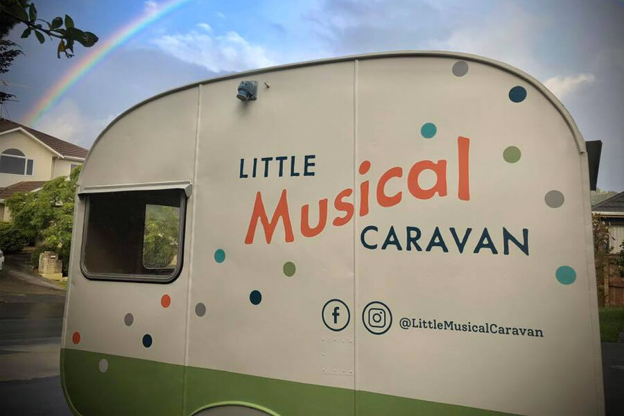 Retro Caravan in front of blue sky with a rainbow